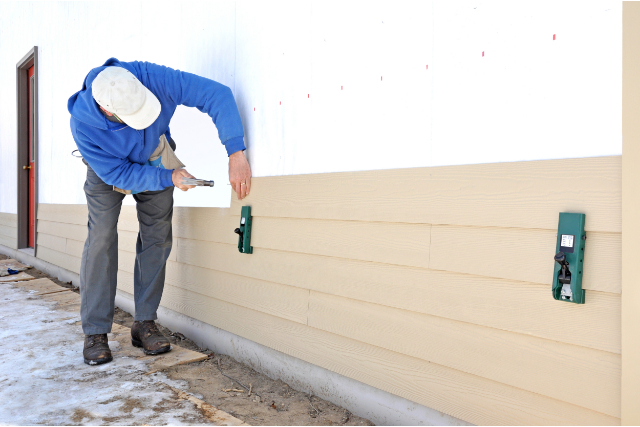 Siding Installation by worker with hammer and nails