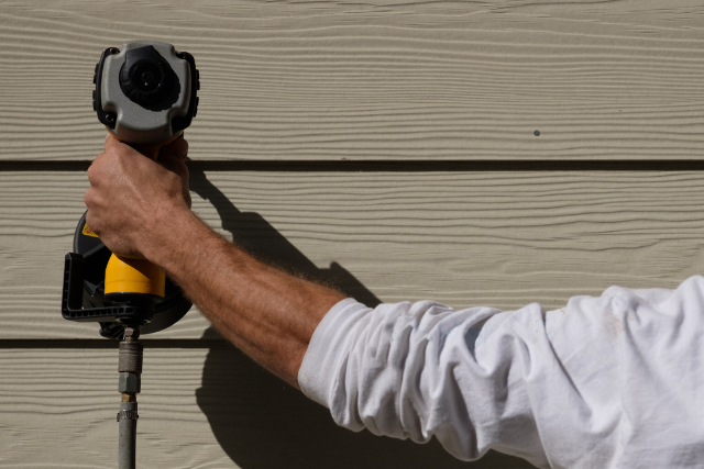 Siding Installation by worker with power tool